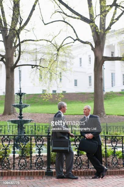 Businessmen talking together in park