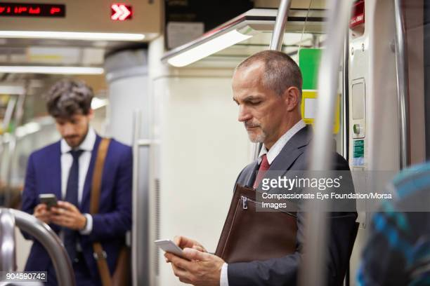 Businessmen texting on cell phones on subway train