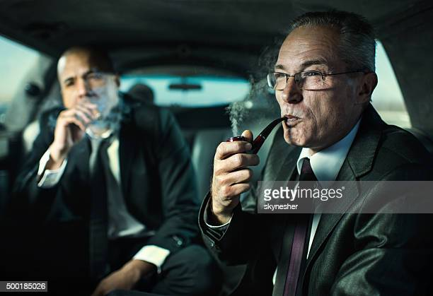 Businessmen traveling in a limousine and smoking.