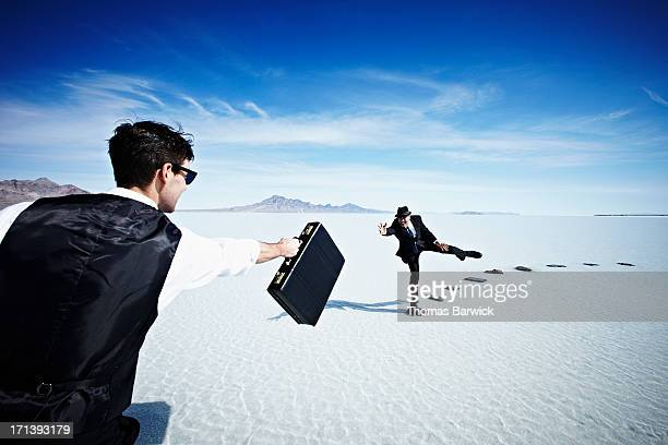Businessmen trying to pass briefcase across gap