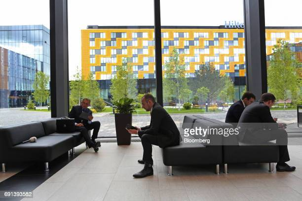 Businessmen use mobile devices in the main hall during the St Petersburg International Economic Forum at the Expoforum in Saint Petersburg Russia on...