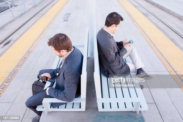 businessmen using cell phones at train station - 背中合わせ ストックフォトと画像