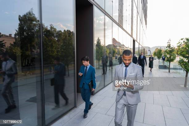 businessmen using digital tablet and smart phone - gray suit stock pictures, royalty-free photos & images