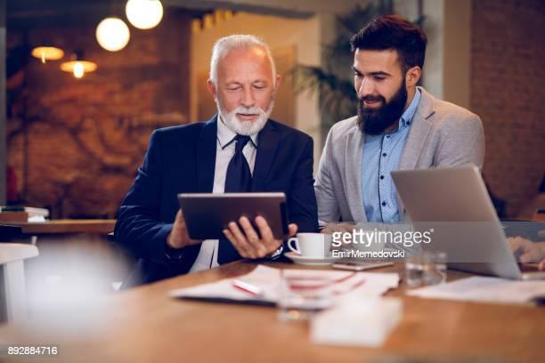 Businessmen using digital tablet in cafŽ