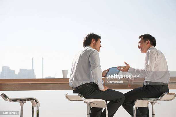 businessmen using digital tablet in meeting - face to face stock pictures, royalty-free photos & images
