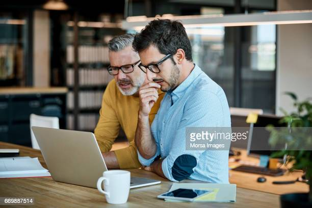 businessmen using laptop at desk - business casual stock pictures, royalty-free photos & images