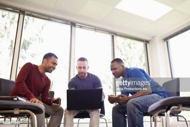 Businessmen using laptop in office meeting