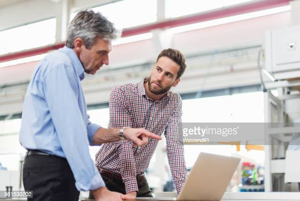 businessmen using laptop in production hall - fortschritt stock-fotos und bilder