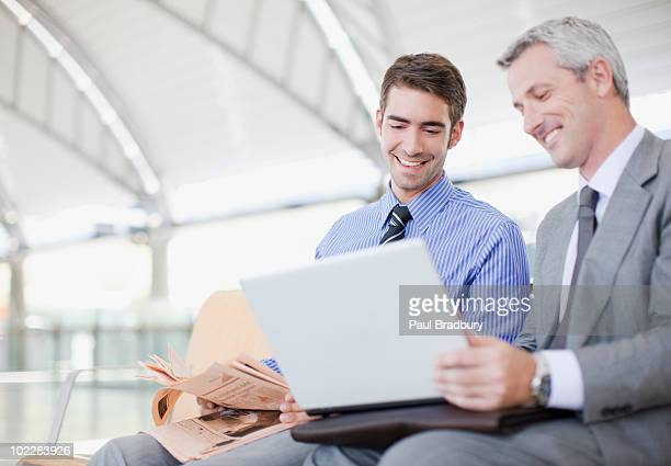 Businessmen using laptop in train station waiting area