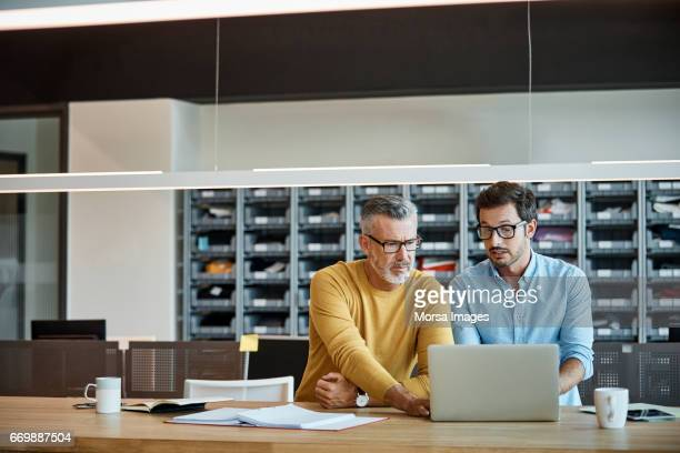 Businessmen using laptop together at desk