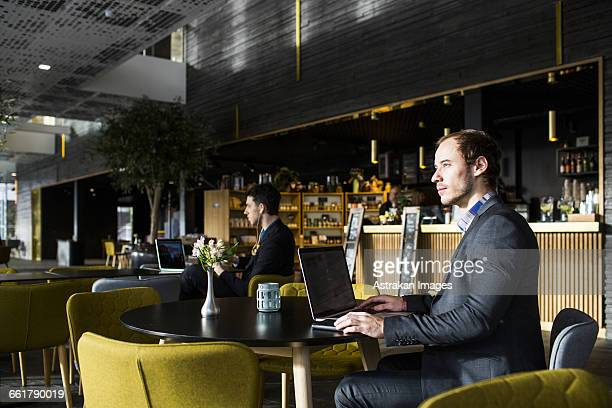 Businessmen using laptop while sitting at table by counter in restaurant