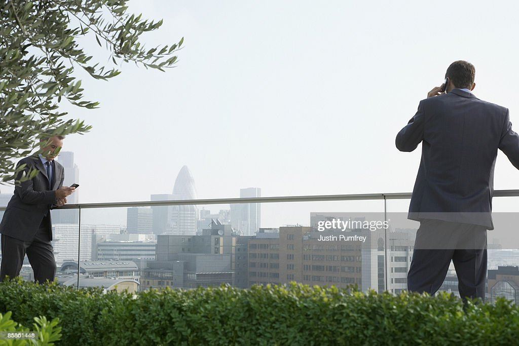 Businessmen using mobiles on rooftop : Stock-Foto