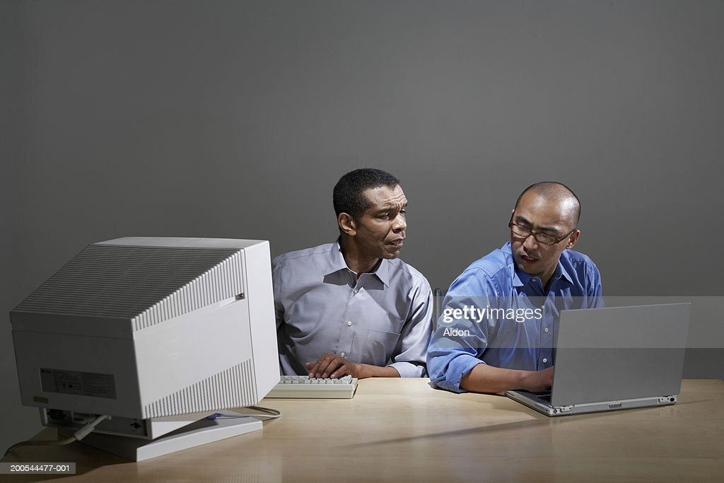 Businessmen using old and new computer technology : Stock Photo