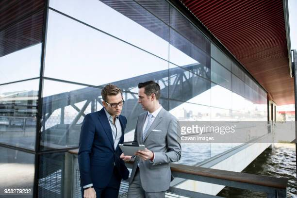 businessmen using tablet computer while standing outside building - cavan images foto e immagini stock