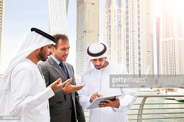 Businessmen using tablet in Dubai Marina.
