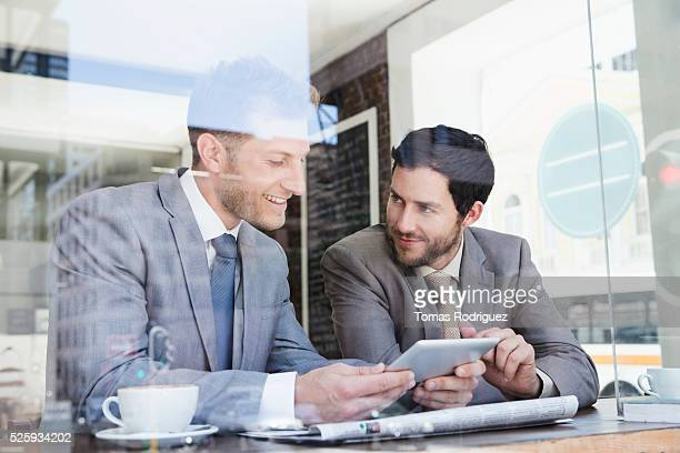 Businessmen using tablet PC in cafe