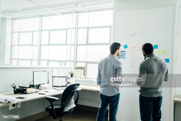 businessmen using whiteboard in office - back to work stock pictures, royalty-free photos & images