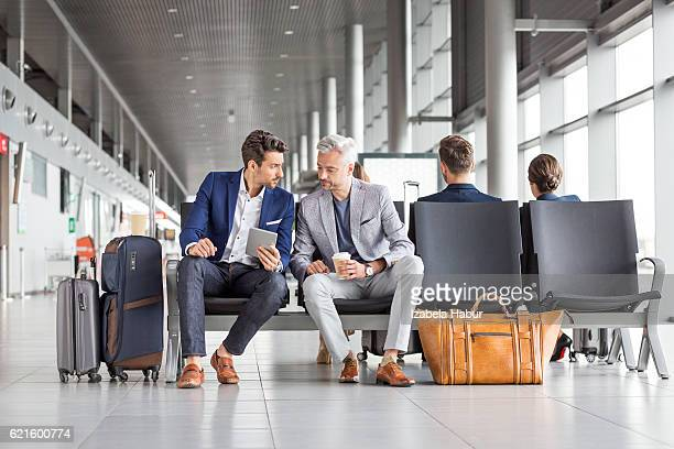 businessmen waiting for their flight - geschäftsreise stock-fotos und bilder