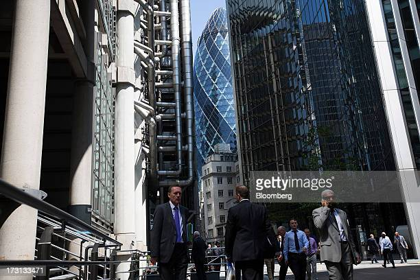 Businessmen walk near the Lloyd's of London building home of the Lloyd's insurance market left the Swiss Re building also known as the 'Gherkin'...