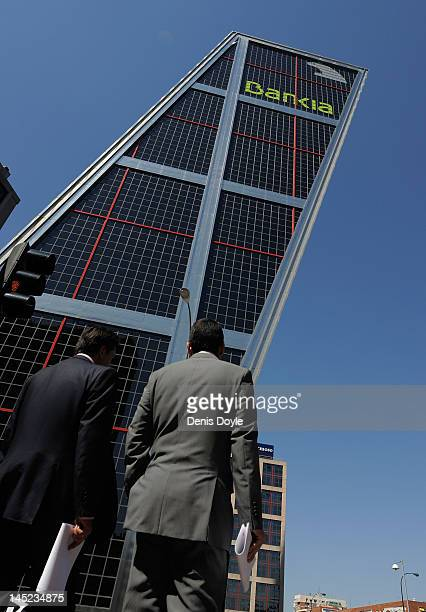 Businessmen walk torards the headquarters of the troubled Spanish savings bank Bankia on May 24 2012 in Madrid Spain Spain's ailing economy struggles...
