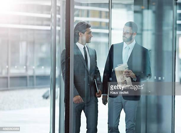 Businessmen walkin & talking threw swing door