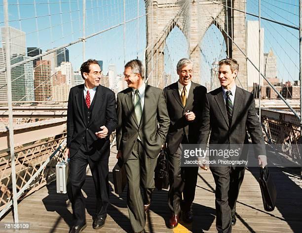 Businessmen walking across bridge