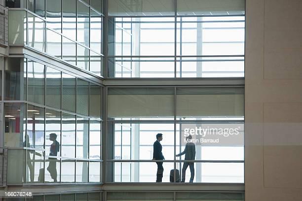 ビジネスマンに沿って歩くで現代的なオフィスの廊下