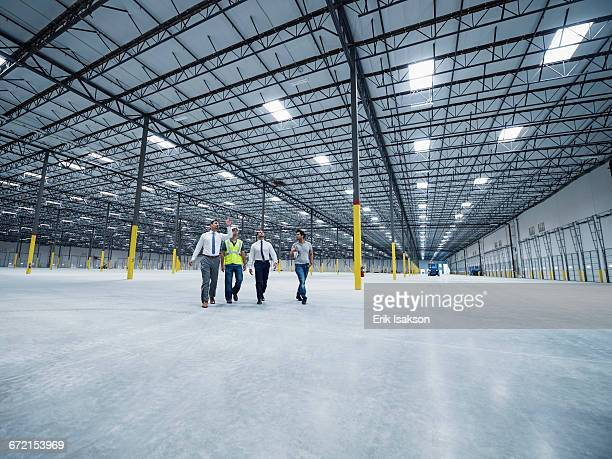 Businessmen walking and talking in empty warehouse