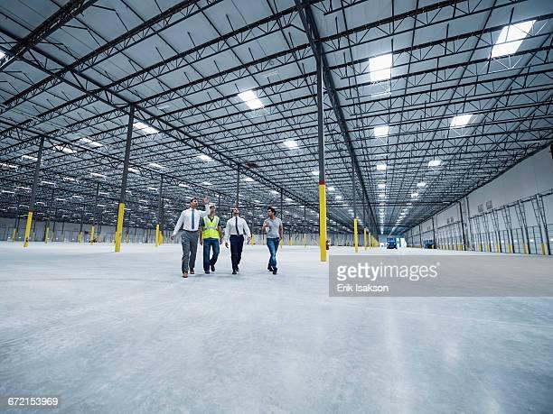 businessmen walking and talking in empty warehouse - 工業施設 ストックフォトと画像