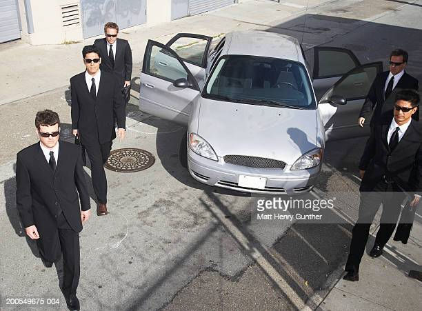 Businessmen walking away from car