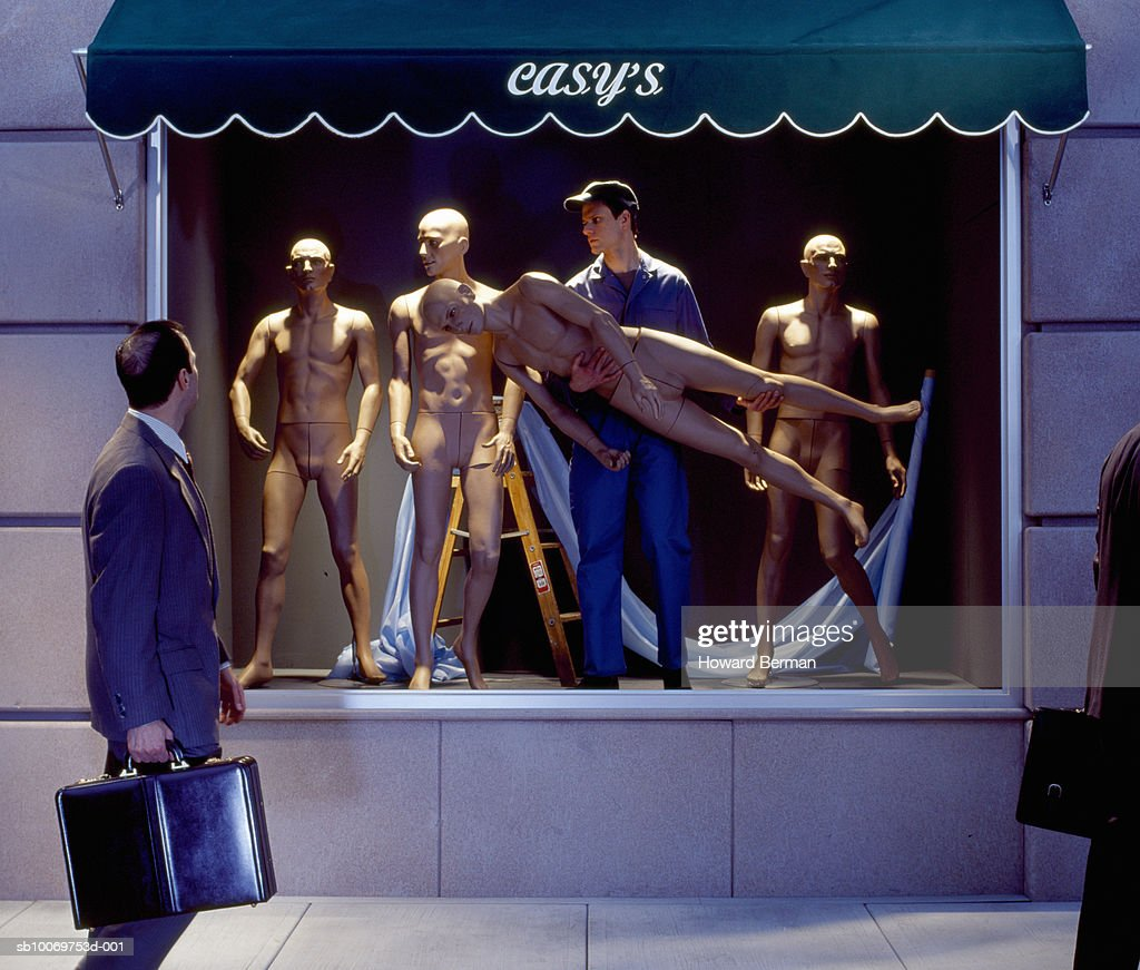 Businessmen walking by mannequins worker : Stock Photo