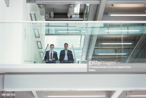 Businessmen walking down stairs in modern office