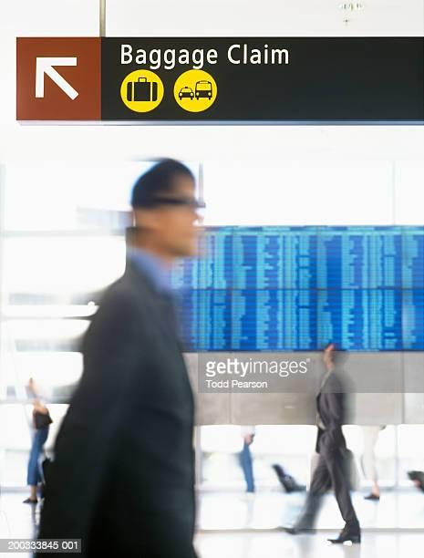 Businessmen walking in front of flight schedule board, blurred motion