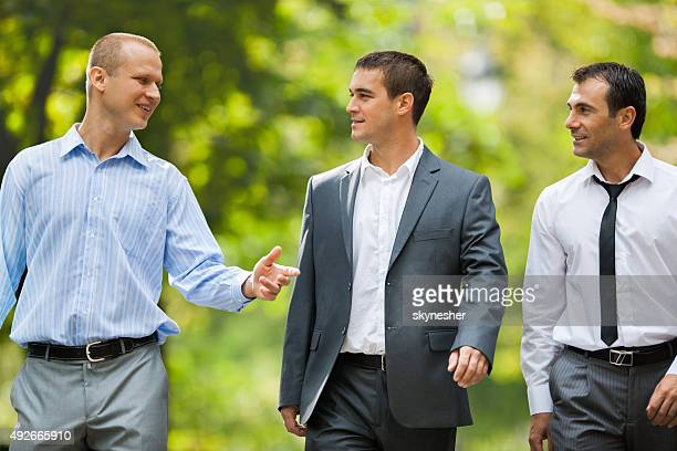 Businessmen walking in the park and communicating.