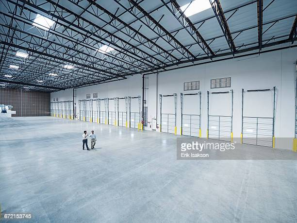 Businessmen walking near loading docks in empty warehouse