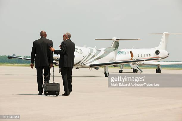 Businessmen walking on airport tarmac