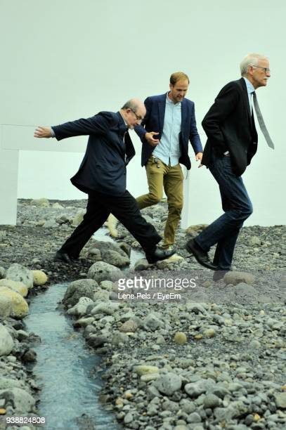 businessmen walking on rocks against wall - lene pels stockfoto's en -beelden