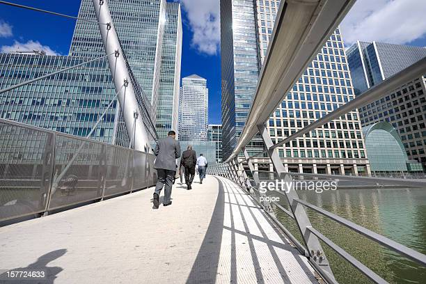 businessmen walking on south quay footbridge, canary wharf, london uk - london docklands stock pictures, royalty-free photos & images