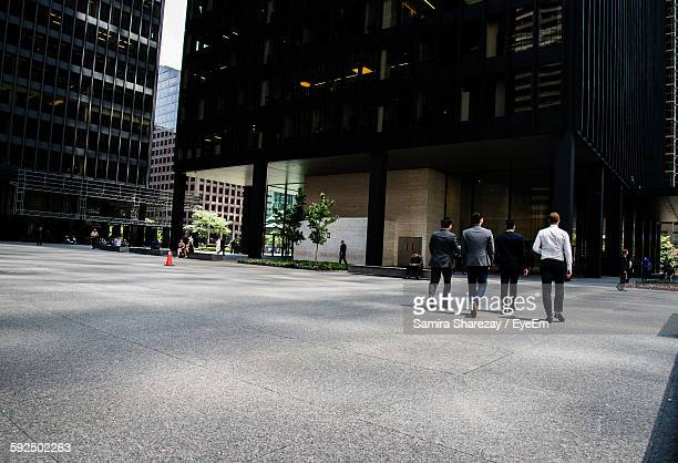 Businessmen Walking On Street In City
