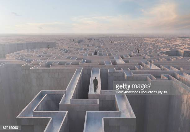 Businessmen walking on top of complex maze
