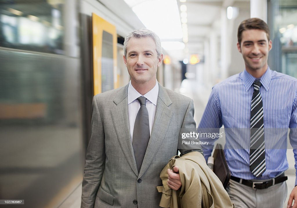 Businessmen walking on train platform : Stock Photo
