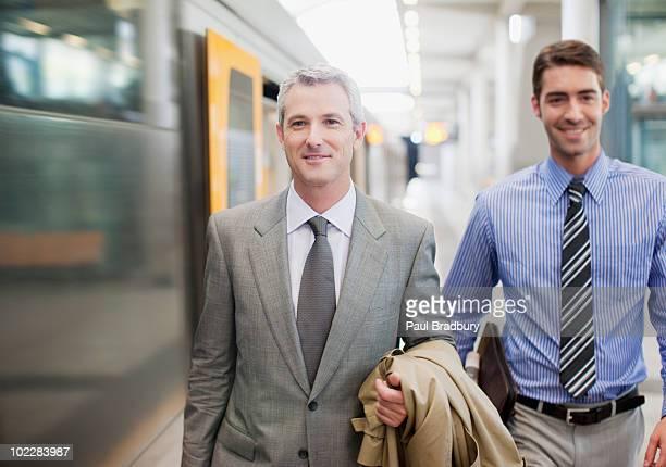 Businessmen walking on train platform