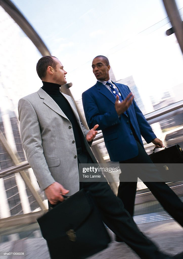 Businessmen walking together inside, bulidings through window in background : Stockfoto