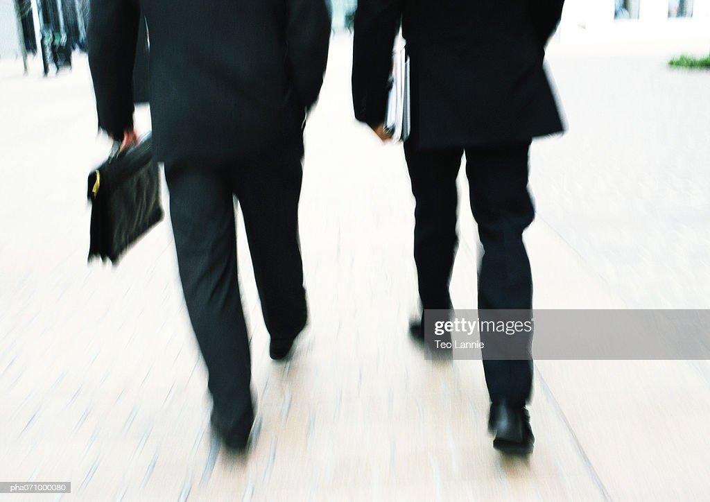 Businessmen walking together, lower section, blurred. : Stockfoto