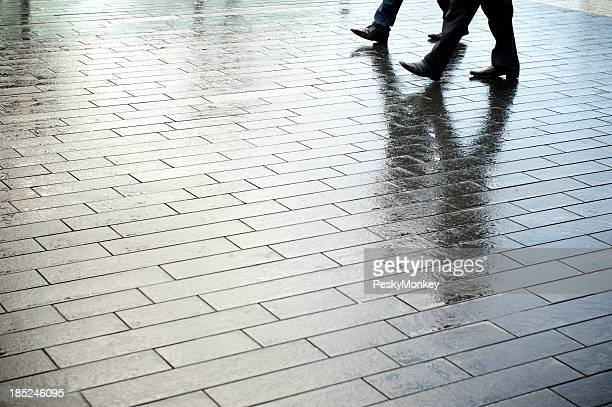 Businessmen Walking Together Outdoors on Textured Wet Pavement