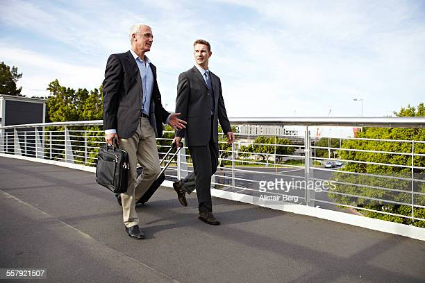 businessmen walking together - gemeinsam gehen stock-fotos und bilder