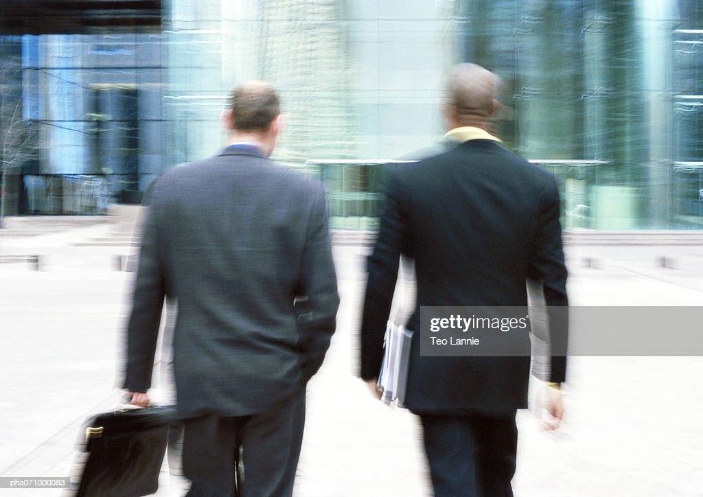 Businessmen walking towards building, rear view, blurred. : Stockfoto