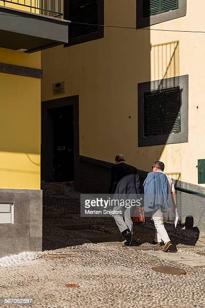 businessmen walking up alley in shadow - merten snijders stock pictures, royalty-free photos & images