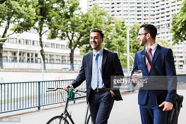 Businessmen walking with bicycle in the city, talking