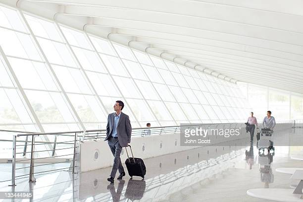 businessmen walking with luggage at airport - geschäftsreise stock-fotos und bilder